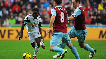 Swansea's Nathan Dyer takes the ball past West Ham's Razvan Rat and Kevin Nolan during the Barclays
