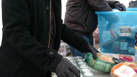 Men from the Muslim community sort donations of food and clothing to give to homeless people in Ilfo