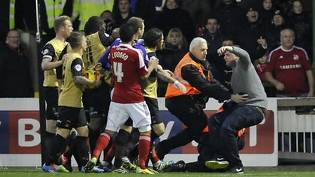 A Swindon Town fan is tackled by a steward after invading the pitch. PA