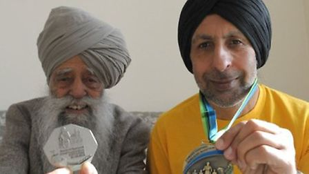 Fauja Singh and Harmander Singh displaying medals they have been awarded for taking part in a recen