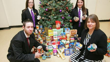 Damien McCabe, Lauren O'sullivan and Amy O'sullivan present the tinned food to Kim Marry from Hope