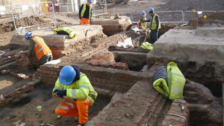 Archaeologist excavating the remains of Rokeby House with the foundations of the Empire Theatre to t