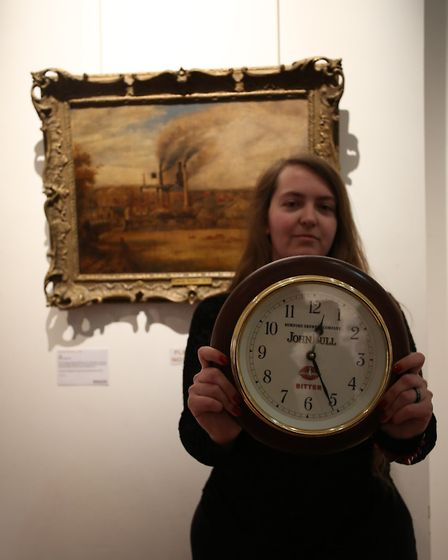 Chloe Branwhite with a 1980s clock loaned to the Museum by Valerie Wheatland and an 1860s painting o