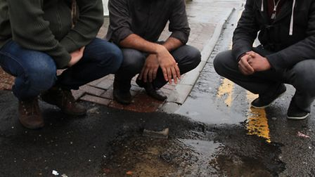 Shopkeepers Mubeen Afzal, left, Umer Rassoon, and Dr. Roaid Khan, centre, complain about a water lea
