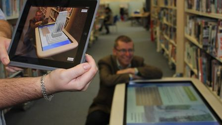 A customer demonstrating how the SMART Table at Romford Central Library works with 3D imaging.
