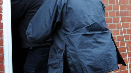 Police enter a house in Operation Big Wing raid.