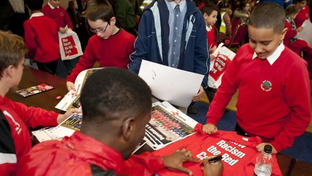 Schoolchildren getting t-shirts signed by the footballers