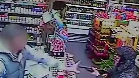 The shop assistant tries to bat away the firearm