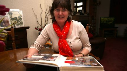 Foster carer Sue Terry looking through a photo album of children she has fostered.