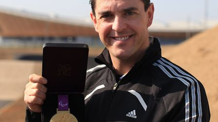 Former paralympian Mark Colbourne shows of his gold medal won in the C1 3km individual pursui