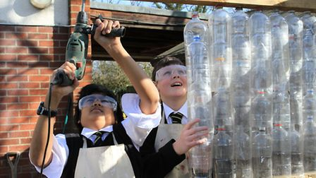 Students busy building the plastic bottle greenhouse at Shenfield High School Vocational Centre. (St