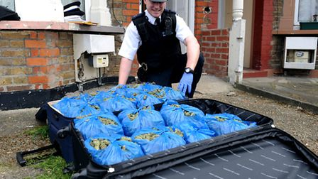 PC Marc Yardley with a suitcase full of dried cannabis plant heads that were found in a Seven Kings
