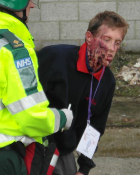A casualty with facial injuries is lead to safety