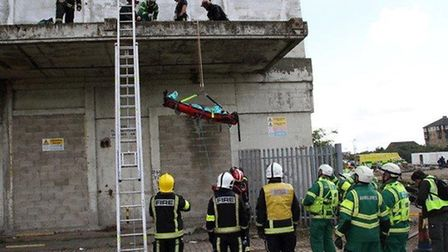"A "" casualty"" is lowered from a ledge of The Milienium Mills buildling in a stretcher after suppos"