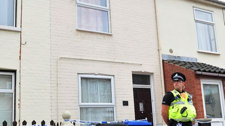 CRIME SCENE: A police officer stands guard outside the house in Cambridge Road, Lowestoft, last July