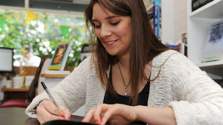 Lily Say, 17, signs a copy of her book