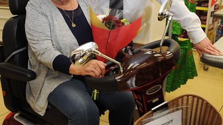 Injured pensioner Patricia Beckford is presented with a cheque and a new mobility scooter by Iceland