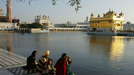 Pilgrims sit at the edge of the moat surrounding the Golden Temple of Amritsar in India's Punjab reg