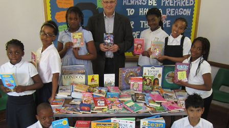 Alick Whitfield from Taylor Woodrow with the books donated to St Luke's Primary School and a group o