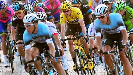 Team Sky's Chris Froome, of Great Britain, in the centre of the peloton as it makes its way along the Champs Elysees...