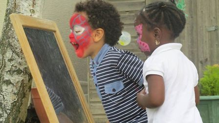 Jacob Osibote, 3, and Demi Alo, 2, admire their newly painted faces