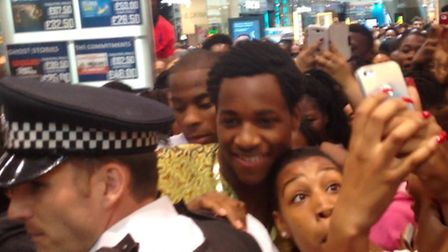 Fans try to take photos with Sam Okafor, centre, as police escort him through Westfield Stratford Ci