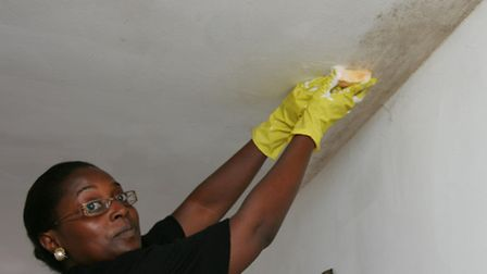 Sadia Nakimera cleans the mould off of her ceiling