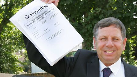 Cllr Jeff Tucker holding up the independent report that cleared him of racist remarks.