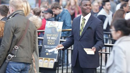 Jehovah's Witnesses engaged in public witnessing with a literature cart. © Watch Tower Bible and Tra
