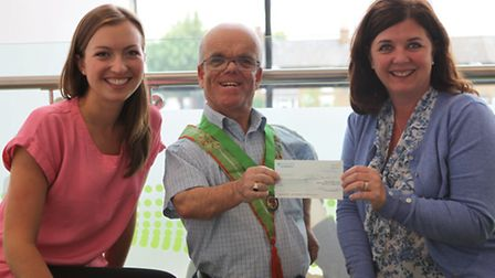 Mark Gill presenting the £1,300 cheque to Alicia Luther-Jones (left) and corporate relationship mana