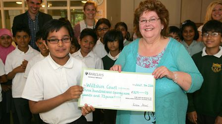The school handing over donation to Wiltshire Court. Vishal Sharma, 11 with Barbara Lowe from Wilts