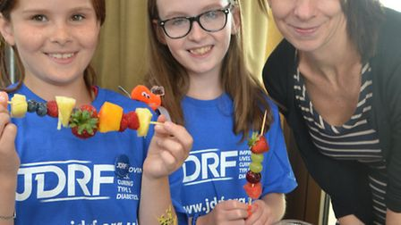 Bella and Phoebe Radley make fruit kebabs with paediactric diabetes diatician Kate Nelson