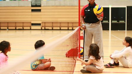 Maurillia teaches sitting voleyball to children on the Fit For Sport summer camp at the Copper Box A