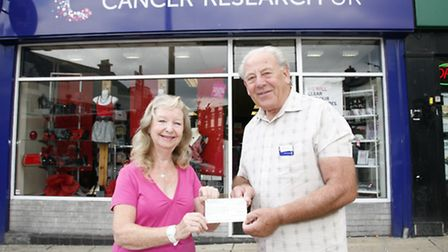 Maureen Wooderson hands the money to Roger Moore, volunteer at Hornchurch Cancer Research