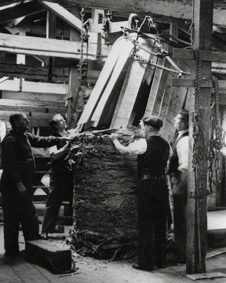 The staves of a hogshead of tobacco being removed before it is weighed at the Royal Victoria Dock, t