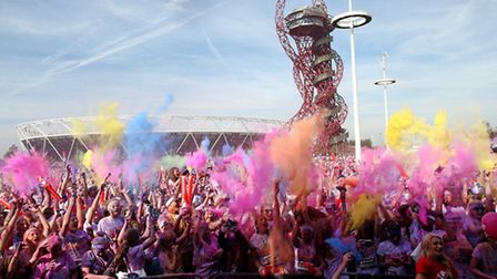 Runners celebrate in The Color Festival Area after the 5km Color Run at Queen Elizabeth Olympic Park
