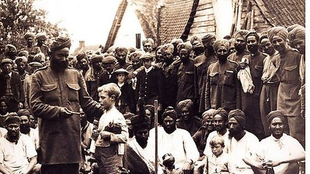 Men from the 15th Sikh Regiment spend time with the locals in a Flanders village after weeks in the