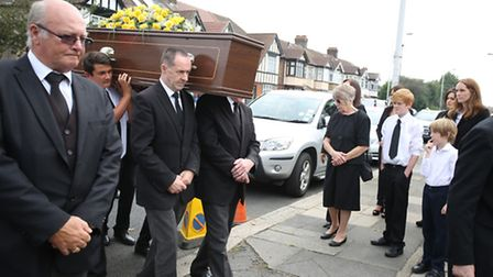 Friends and family look on as pallbearers carry Graham Borrott's coffin towards St Peter's Church, A