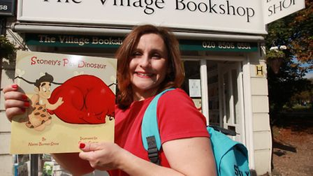 Children's author Naomi Burman-Shine outside The Village Bookshop, Woodford Green, with a copy of he