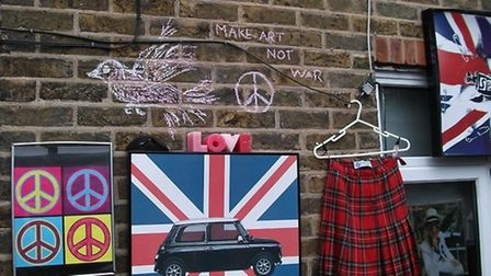 Jean Lane's work in Rectory Crescent. She used symbols of peace and 1960s rock and roll items, inclu