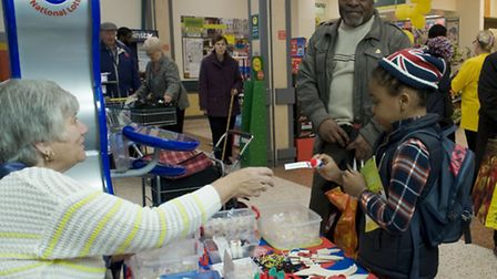 Local residents buying a poppy from Betty Hill's stall in Morrison's Stratford (photo: Arnaud Stephe