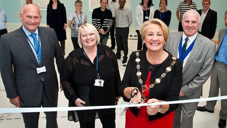 The Mayor cuts the ribbon in the presence of councillors library staff and the building contractors