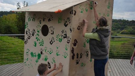 Helpers put hand prints on the bird box at Chafford Gorges