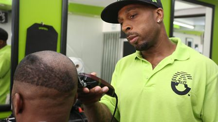 Patrick cuts hair in his barber's shop in Barking Road