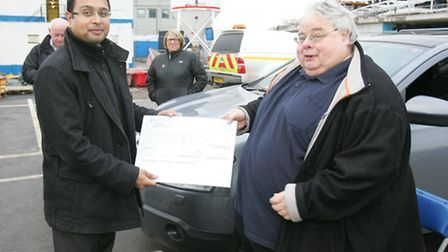 Davendra Dabasia presents a cheque to Kevin Jenkins