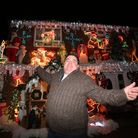 Bill Bates poses with Christmas lights display outside their house to raise money for Haven Hospice