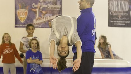 Coach Gareth Green helps reporter Janine Rasiah with a back hand spring drill