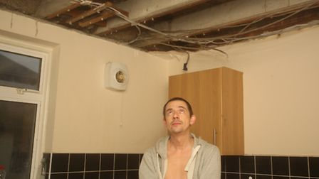 Keith Porter in the kitchen in his and his partner's Louise Hart flat where the ceiling caved in on