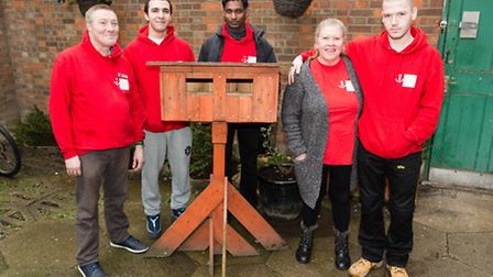 Former and current residents pose with a birdbox in the garden at Anchor House in Barking Road, Lond