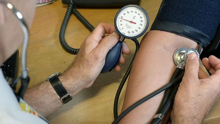 A GP checking a patient's blood pressure.